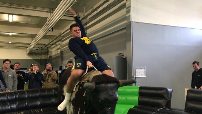 Michigan offensive lineman Jon Runyan Jr. rides a mechanical bull after paintball in France.