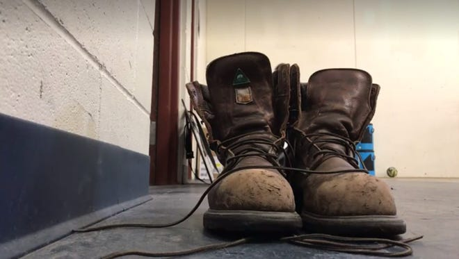 Work boots, owned by Shreveport Mudbugs assistant coach Jason Campbell, sit outside the team's locker room at Fogerty Arena in Blaine, Minnesota. The Mudbugs are vying for a Robertson Cup championship this weekend.