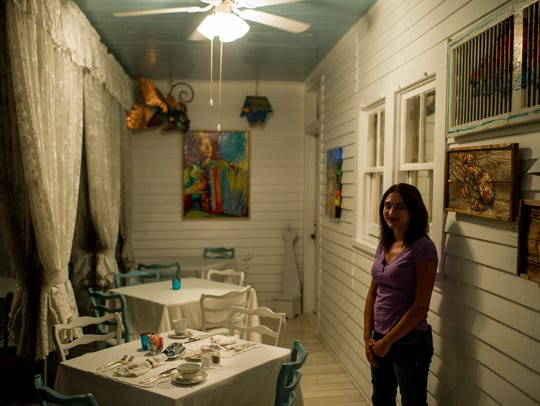 Holly Trahan leads a tour through a dining porch at