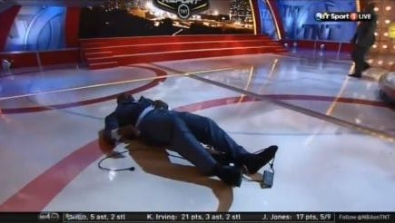 Shaquille O'Neal lays on the ground after falling off the riser on the set of TNT's NBA halftime show.