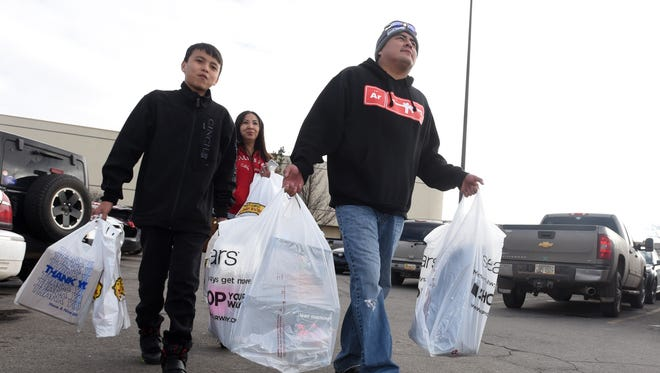 Orren Bernal, 12, left, his dad, Warren Bernal, right, and mom, Cheryl Bernal, head to their car to unload Christmas presents on Dec. 24, 2015, at the Animas Valley Mall. City officials in Farmington and Bloomfield are planning a lawsuit against the New Mexico Taxation and Revenue Department over an alleged lack of transparency in gross receipts tax distributions.
