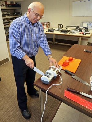 Sam Weiner, president of EdgeCraft Corp., which makes Chef'sChoice knives and cooking appliances, demonstrates how a ceramic knife is sharpened in one the company's high-end sharpeners. The company was acquired by the Legacy Cos. on Monday.
