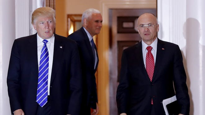 FILE - In this Nov. 19, 2016 file photo, President-elect Donald Trump walks Labor Secretary-designate Andy Puzder from Trump National Golf Club Bedminster clubhouse in Bedminster, N.J. Puzder was CEO of a fast food empire that is outsourcing jobs on his watch, a stark contrast with his boss' threats and tweeted slaps at companies that outsource jobs.  (AP Photo/Carolyn Kaster, File)
