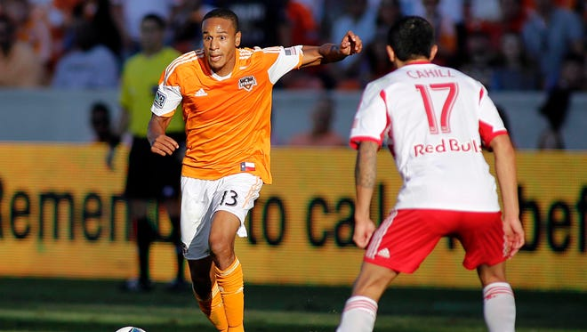 Houston Dynamo midfielder Ricardo Clark (13) passes the ball past New York Red Bulls midfielder Tim Cahill (17) during the second half of the eastern conference semifinal game at BBVA Compass Stadium.