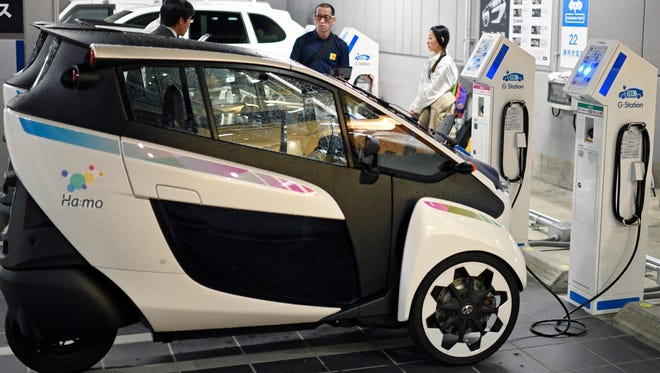 Toyota's compact three-wheeled electric vehicle 'i-Road' is parked at a pick-up station in central Tokyo,