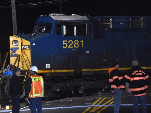 Emergency responders surround the engine of a train