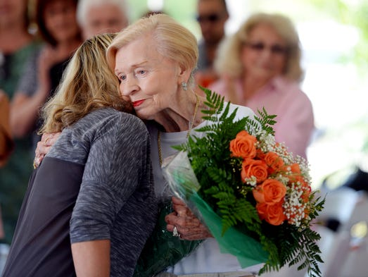 Kay England (right) receives a hug and a bouquet of