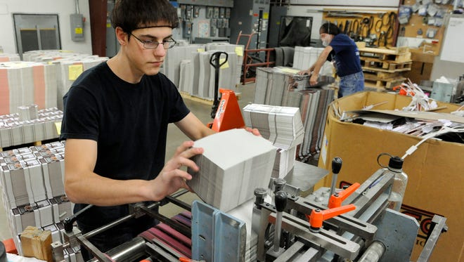 Brandon Swoboda, 19, feeds a gluing machine with Hershey's chocolate pudding boxes at Color Craft Graphic Arts in Manitowoc.