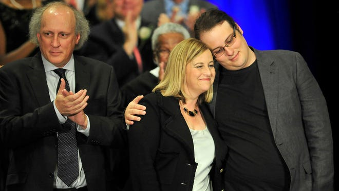 Mayor Megan Barry, center, gets a hug from her son Max during an inaugural ceremony at Music City Center in Nashville, Tenn., Friday, Sept. 25, 2015. At left is her husband Bruce Barry.