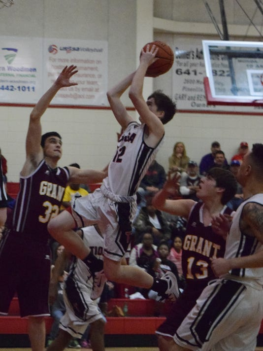 Tioga's Dustin Roy (12, center) scores two points against Grant Tuesday.