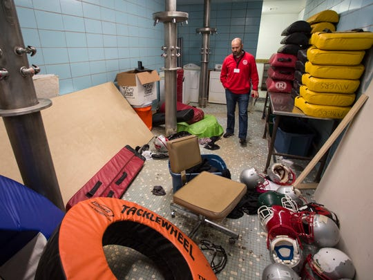 Waggener Traditional High School athletic director Jamie Dumstorf looks inside one of the shower areas in the sports complex. Many of the former showers in the sports complex at Waggener have been out of commission for more than a decade. Today, they have become impromptu storage areas for much of the athletic equipment due to lack of space.