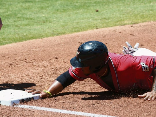 El Paso's Rymer Liriano slides back safely to first base ahead of a pickoff attempt on Sunday.