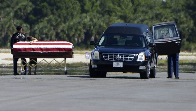"""A family member embraces the casket with the body of Sgt. 1st Class Pablo A. """"Ponch""""' Ruiz as he arrives at Melbourne International Airport Thursday morning.  Ruiz died while serving in Afghanistan."""