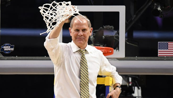 Michigan coach John Beilein celebrates with the net after the Wolverines beat Florida State to reach the Final Four.