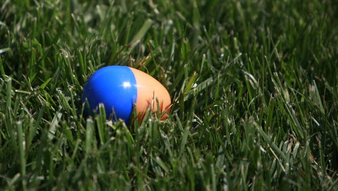 An Easter egg filled with candy waits for a kid to find it.