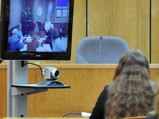 Sara Anne Woody, 25, watches as closed circuit television testimony is given by her stepson, an alleged victim, Thursday morning in the 30th District Court. Woody is charged with 26 counts of injury to a child, a first-degree felony. This photograph was altered to protect the identity of the alleged victim.