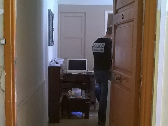 French police officers look for evidences in the flat