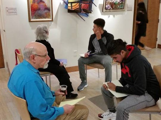 Senior citizen David Lieberfarb speaks with student