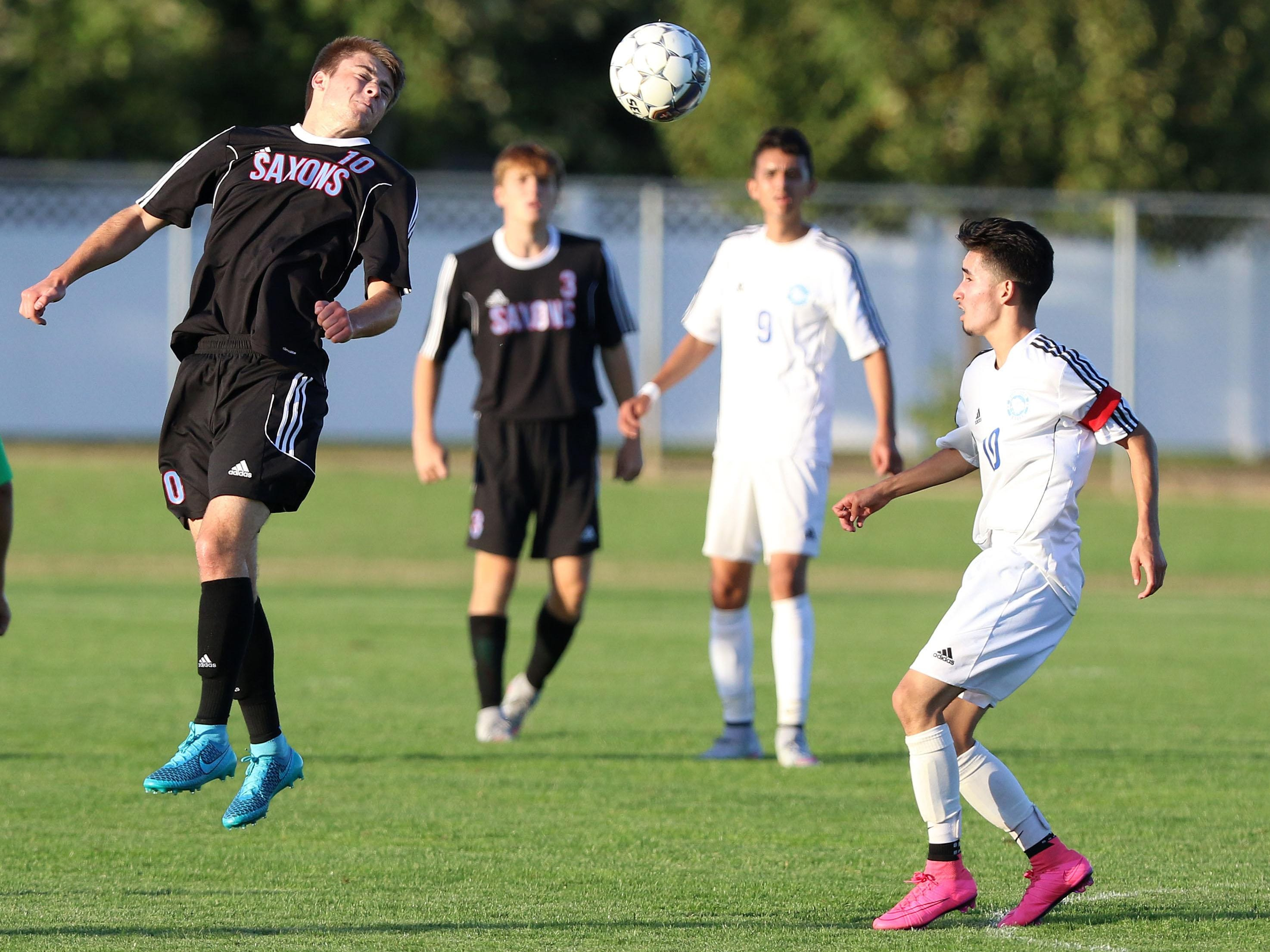 South Salem High School's Isaac Morris heads the ball during their game with Woodburn on Tuesday, Sept. 8, 2015, in Woodburn.