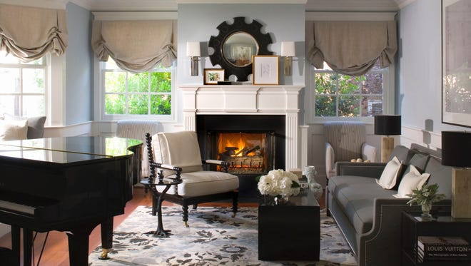 A living room designed by Betsy Burnham, where carefully chosen pieces of black furniture and black accents bring out the beauty of the softer, neutral shades of white and tan.
