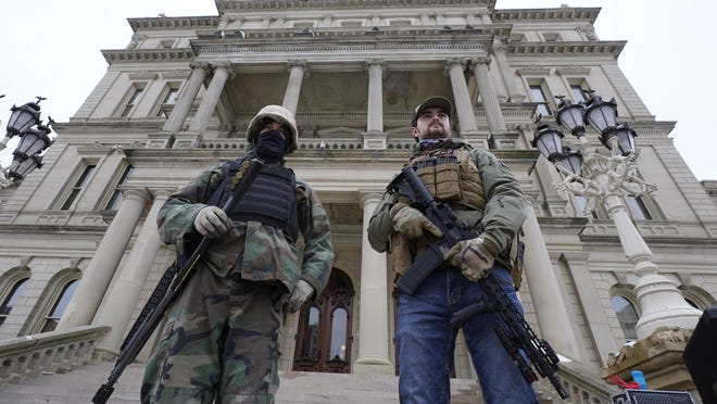 Men with a shotgun and a rifle stand on the steps at the state Capitol after a rally in support of President Donald Trump Wednesday in Lansing.
