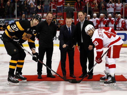 Members of the 1997-1998 Detroit Red Wings' Grind Line (left to right) Joey Kocur, Kris Draper and Kirk Maltby ceremoniously drop the puck between Zdeno Chara of the Bruins and Henrik Zetterberg of the Red Wings at Joe Louis Arena on Jan. 18, 2017.