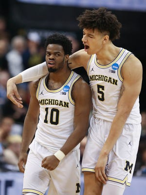 Michigan Wolverines Derrick Walton Jr., left, and D.J. Wilson celebrate a basket against Oklahoma State during the second half of U-M's 92-91 win Friday, March 17, 2017 at Bankers Life Fieldhouse in Indianapolis in the NCAA tournament.