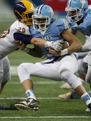 Warren De La Salle's Cooper Gammon tackles Muskegon Mona Shores' Tyree Jackson during first half action in the Division 2 state championship game on November 28, 2014 at Ford Field in Detroit.