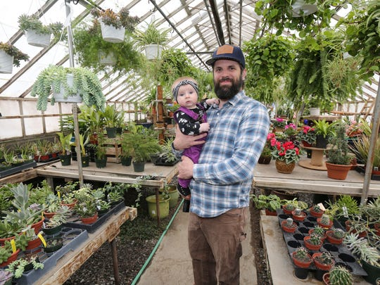 Matthew Sabellico, the head grower at the family run Sabellico Greenhouses in Hopewell Junction, holds his 5-month old daughter Freya, in the houseplant greenhouse on the property, March 25, 2017.