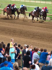 Horses and riders compete in the third race of the day at Ellis Park's opening day Saturday.
