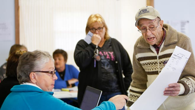 """Verlin Shaver, 92, of Charlotte gets his ballot from a precinct official on Tuesday, Nov. 8, 2016.  """"I've voted every election, but this year, there's no one to vote for,"""" Shaver joked; """"I'll probably vote for Trump though,"""" he said."""