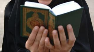 A Lebanese woman supporter of Hezbollah, reads the Islamic Holy book, the Quran.