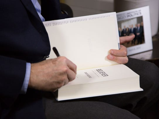 """David Axelrod signs a copy of his new book, """"Believer:"""