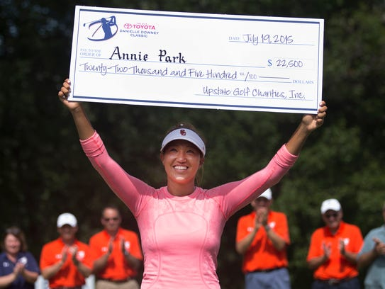 Annie Park holds up the winning check after winning
