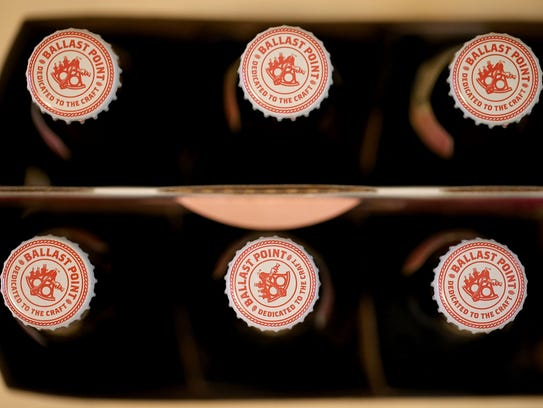 Bottles of Ballast Point beer sit on a shelf. New York-based