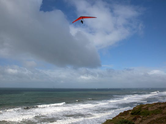 Hang gliders soar over the ocean at Ft. Funston in