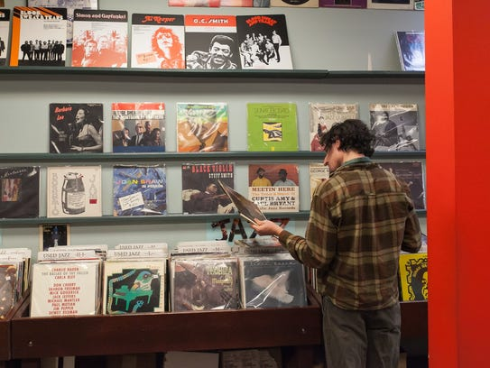 A customer browses through vintage jazz LPs at Street