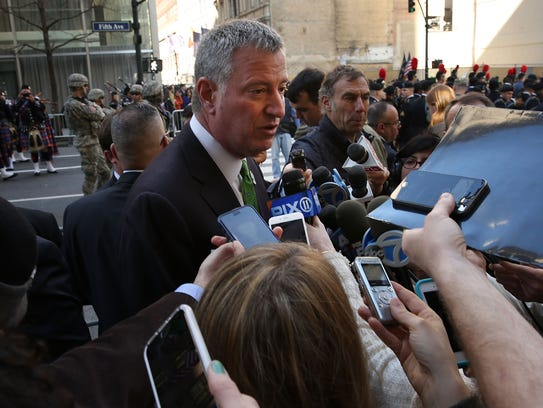 New York Mayor Bill de Blasio talks to reporters earlier