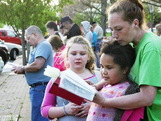 Raychel Bacon, right, of Coshocton, reads from the
