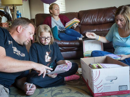 Ava Hutchinson reads birthday cards with her dad Kris,