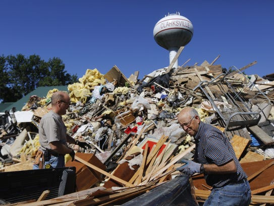 John Scheidecker removes debris from his pickup with help from his brother-in-law Doug Prigge during flood cleanup in Clarksville, Iowa, on Sept. 26, 2016.