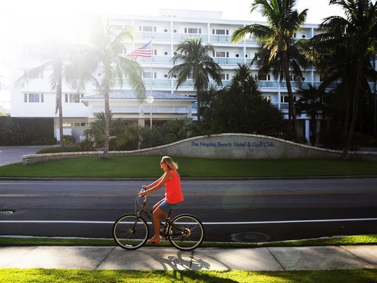 A woman rides her bicycle outside the Naples Beach