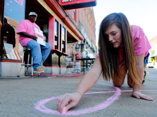 Rivers Landrum draws a pink ribbon on the side walk