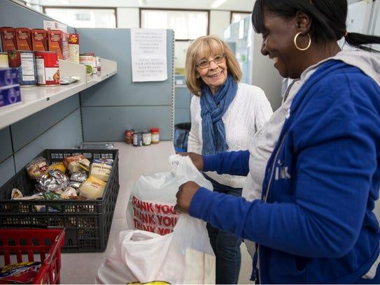 Volunteer Maryann Pucilowski helps Beverly Fitzpatrick
