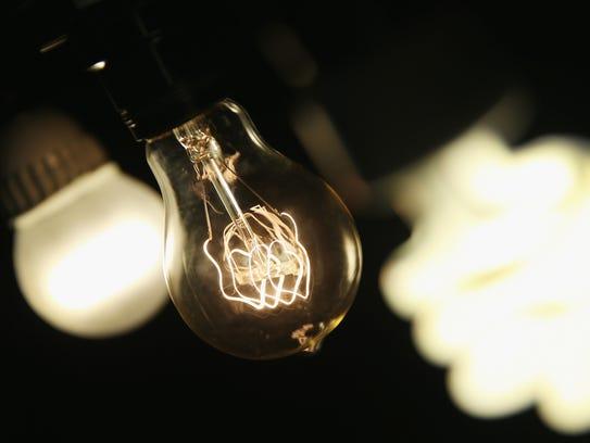 A vintage-style incandescent light bulb, center, is