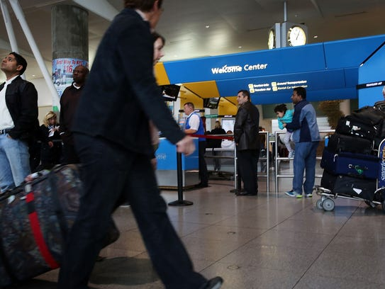 Travelers are seen arriving at the international arrivals