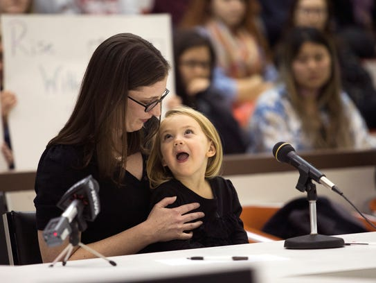 Mary Robinson, with daughter Catherine, 3, speaks in