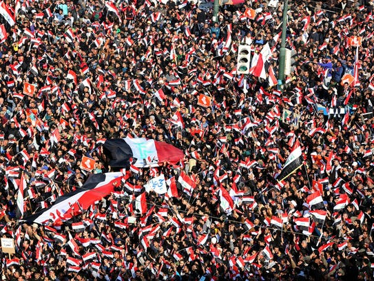 Supporters of Iraqi Shiite cleric Muqtada al-Sadr wave