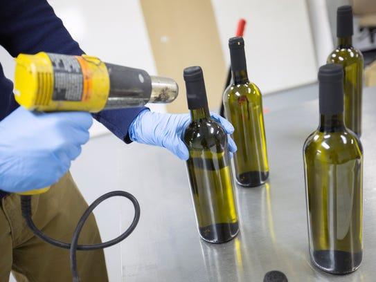 Kaelan Castetter uses a heat gun to seal bottles of