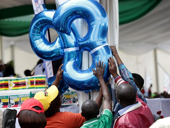 Youths put up a 93 decoration to mark Zimbabwean President